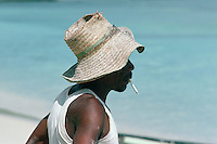 A fisherman relaxes with a cigarette after landing his catch and bringing it to the informal market on Beau Vallon Bay beach.