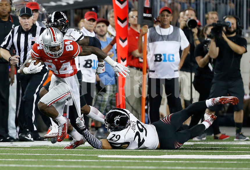 Ohio State Buckeyes wide receiver Corey Smith (84) gets dragged down by the undershirt by Cincinnati Bearcats safety Andre Jones (29) during the fourth quarter of the NCAA football game at Ohio Stadium in Columbus on Sept. 27, 2014. (Adam Cairns / The Columbus Dispatch)