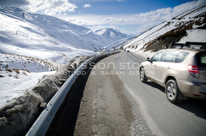 SUV and cars on the dangerous Crown Range road between Queenstown and Wanaka. Winter time, snow and grit on road,  Sunny day looking down Cardona valley.