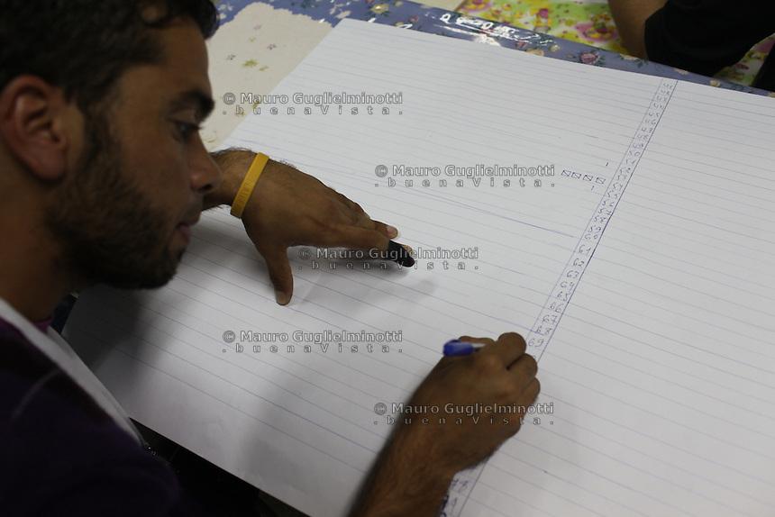 23 ottobre 2011 Tunisi, elezioni libere per l'Assemblea Costituente, le prime della Primavera araba: un osservatore nazionale in un seggio scrive su un quaderno. Ha il dito macchiato di inchiostro nero, segno che ha votato.<br /> premieres elections libres en Tunisie octobre <br /> tunisian elections