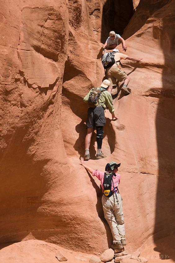Hikers climbing into the entrance of Peekaboo Canyon