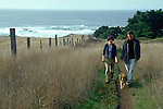 Young couple walking dog on coastal trail near Mendocino California