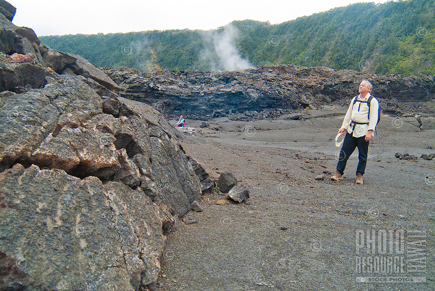 A hiker views a stack of broken lava sheets while another in the distance feels the heat from an underground active volcano as hot steam rises from the floor of Kilauea Iki Crater (a 1959 lava lake) in Hawai'i Volcanoes National Park, Big Island.