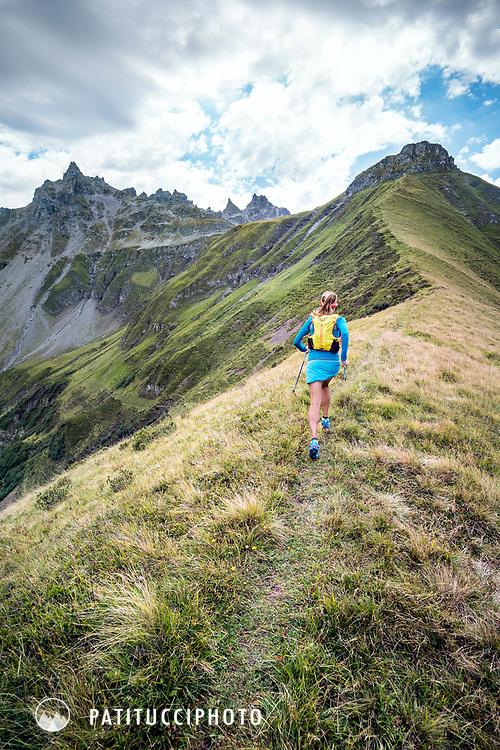 Trail running on a grassy mountain trail above the Weisstannental, near the Pizol, Switzerland