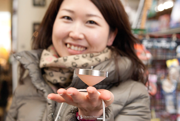 A young Japanese lady displaing a Japanese spinning top in Osu, the trendy shopping district for young people of Nagoya city.