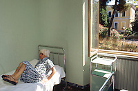 Italy. Province of Lazio. Rome. Santa Maria della Pieta is an asylum for mentally handicapped people. An old woman with grey hair lies on her bed alone in her room. Mental hospital. Lunatic asylum. Psychiatric hospitals, also known as mental hospitals, are hospitals specializing in the treatment of serious mental disorders. Santa Maria della Pieta is specialised in the temporary or permanent care of residents who, as a result of a psychological disorder, require routine assistance, treatment, or a specialised and controlled environment. Patients are often admitted on a voluntary basis, but involuntary commitment is practiced when an individual may pose a significant danger to themselves or others. 10.07.97 © 1997 Didier Ruef