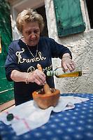 Europe/France/Provence-Alpes-Côte d'Azur/13/Bouches-du-Rhône/Marseille: Préparatifs du repas au cabanon d'Yves Darnaud, cabanonier à la Calanque de Sormiou - Yvetet prépare l'Aïoli - Yvette Kevran Auto N: 2009-107