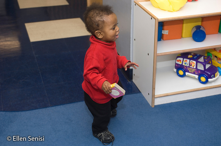 MR / Schenectady, NY.Schenectady Day Nursery / private non-profit daycare center / Infant Class.Toddler (boy, 1, African-American / Hispanic) who has just learned to walk, practices his new skill while holding a toy..MR: Leo4.© Ellen B. Senisi