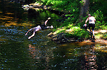 Several young men take turns jumping into a deep spot in the Scantic River in in their attempt to get  relief from the 102 degree temperature at mid afternoon, Friday, July 22, 2011, in Enfield. (Jim Michaud/Journal Inquirer)