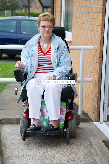 Older woman wheelchair user leaving her house to go out,