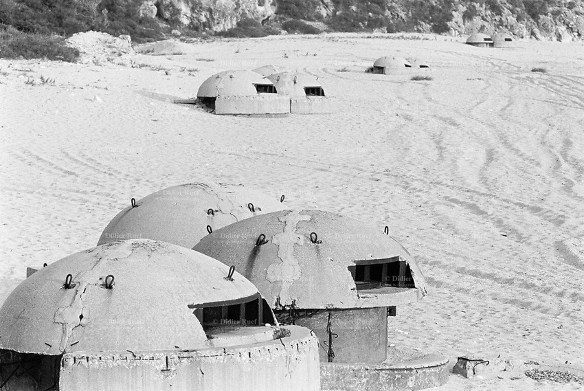 Albania. Province of Vlora. Dhermi. Old derelict bunkers on the beach near the Mediterranean sea front. Enver Hoxha (1908-1985) was for 40 years a dictator and a communist leader. He decided after the historic break with Russia in 1961 to protect his country from any invaders by investing in a massive fortification (more than a million bunkers were built over the years till 1985). © 2003 Didier Ruef