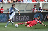 LA Galaxy midfielder Hector Jimenez (16) plays the ball after Chicago midfielder Chris Rolfe (18) unsuccessfully attempts to slide tackle the ball away.  The LA Galaxy defeated the Chicago Fire 2-0 at Toyota Park in Bridgeview, IL on July 8, 2012.