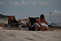 A woman takes a sun bath next where a massive fire that engulfed dozens of businesses along a boardwalkin in Seaside Park September 13, 2013 by Kena Betancur / VIEWpress