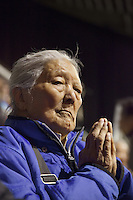 Switzerland. Basel. St. Jakobshalle. An elderly woman prays during the Buddhist ritual. Avalokiteshvara (Chenresig in tibetan) particularly embodies compassion of a Buddha indiscriminately directed to all sentient beings. Avalokiteśvara is a bodhisattva who embodies the compassion of all Buddhas. Avalokiteśvara is one of the more widely revered bodhisattvas in mainstream Mahayana Buddhism, as well as unofficially in Theravada Buddhism. 8.02.2015 &copy; 2015 Didier Ruef