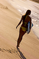 An island girl walks down the beach carrying a surfboard at Big Beach, Makena,  Maui.
