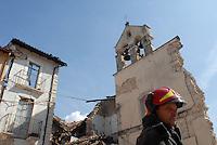 un pompiere davanti ai resti di una chiesa. a fireman and church rests.