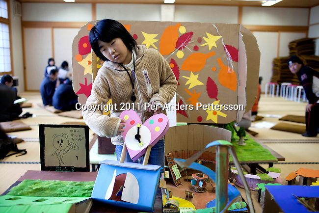 RIKUZENTAKATA, JAPAN - DECEMBER 4: Riu Kono, age 10, shows a model she made during a Save The Children Japan after school program on December 4, 2011, in Rikuzentakata, Japan. Northeastern Japan's coastline was struck by an earthquake measuring 9.0 on the Richter scale and a Tsunami on March 11, 2011 which destroyed villages and livelihoods for hundreds of thousands of people. Almost 16,000 dead, thousands missing, more than 700,000 properties destroyed and an estimated 387,000 survivors lost their homes. Its estimated that it will take more than five years to rebuild. The cost is estimated to 309 billion U.S. dollars, the world's most expensive natural disaster. Many children suffered especially with school destroyed, education interrupted and the loss of family members took a heavy toll. Save The Children Japan runs many programs to assist families and children in the tsunami stricken areas. one of the few ngo's working here they assist with food, hygiene products, shelter, counseling, and many after school and pre school programs and scholarships for families who lost their livelihood after the tsunami. The children has presented these models to the decision makers in the local government in Rikuzentakata. (Photo by Per-Anders Pettersson)