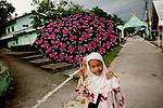 Muslim children walk home along a narrow street on the island of Penyenget, a short boat ride from Tanjung Pinang, Bintan's largest city, in Indonesia, on Tuesday, April 20, 2010.