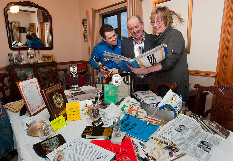 Eileen Breen, former leader at Kilnamona Youth Club, showing some of the old memorabilia from bygone days to Shane Griffin and his father Brendan Griffin. Shane was a member of the club in the 00's and Brendan was also a member in the 70's. Photograph by John Kelly.