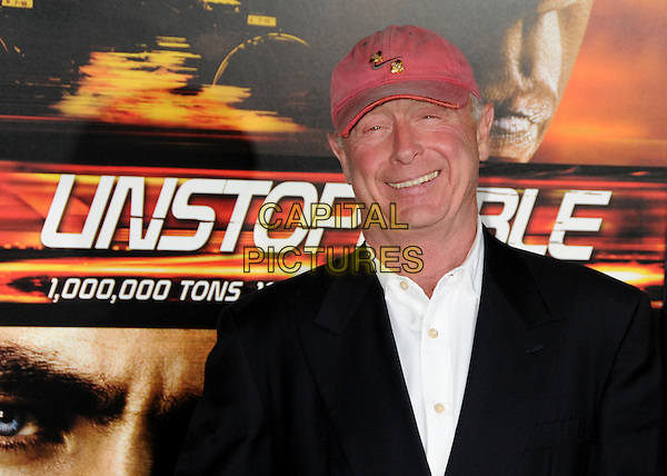 "TONY SCOTT, Director.""Unstoppable"" Los Angeles Premiere held at the Regency Village Theatre, Westwood, California, USA..October 26th, 2010.headshot portrait black white red baseball cap hat smiling.CAP/ADM/BP.©Byron Purvis/AdMedia/Capital Pictures."
