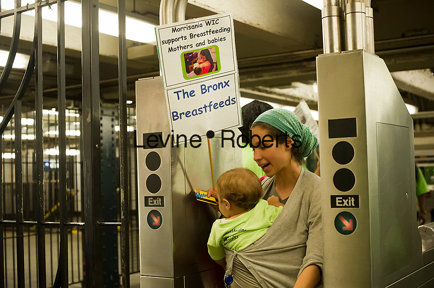 Gillian Tausend and her 10 month old daughter Noa Tausend go through the subway turnstile. Breastfeeding mothers and their supporters participate in a subway caravan to promote breastfeeding and to celebrate World Breastfeeding Week, In New York on Friday, August  10, 2012.   NYC Mayor Michael Bloomberg recently announced that city hospitals will be promoting breastfeeding and discouraging the use of formula.  (© Frances M. Roberts)