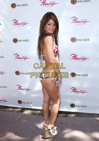 Laura Croft.Laura Croft, in a Kandy Wrappers bikini, hosts at GO Pool at the Flamingo Hotel and Casino, Las Vegas, Nevada, USA..July 17th, 2011.full length white blue red print cleavage belly stomach midriff side looking over shoulder peep toe shoes.CAP/ADM/MJT.© MJT/AdMedia/Capital Pictures.