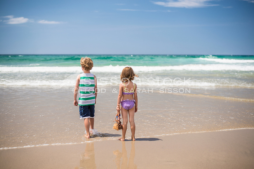 Two children (a boy and a girl) in togs / swimwear running over golden sand towards the beach and sea on a summers day, Whangarei Heads, Northland, New Zealand - stock photo, canvas, fine art print
