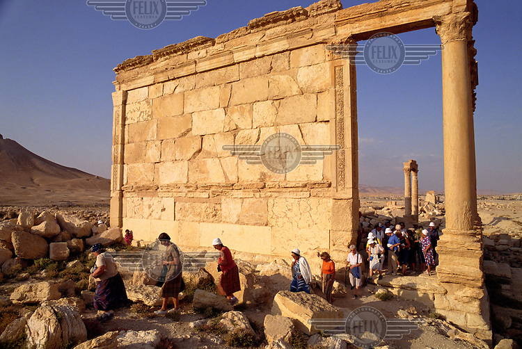 Tourists troupe beneath a part of the famed Roman-era ruins of Palmyra, in the Syrian desert.