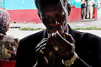 A former Colombian policeman, called El Sheriff, smokes a cigarette before his usual control round in the slum of Calvario, Cali, Colombia, 23 April 2004. Calvario, a slum right in the centre of the city, is considered the social bottom of Cali society. Poor dwellers recollect the garbage in the near city centre to sell it for recycling, while their children get high by sniffing the shoe glue on the dirty streets of ghetto. The order in Calvario is maintained by the illegal authorities, usually former policemen or army members, who set their own rules. Criminality, drug abuse, unemployment never allow the slum people jump off the misery and stop being the second category citizen within the rigid society of Colombia. Although Christian missionary organizations attempt to provide help, the overall situation does not improve.