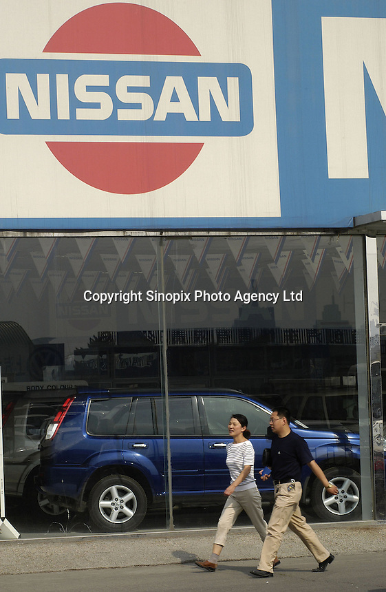 People walk past a Dongfeng Nissan dealership inside a Beijing car market, China..