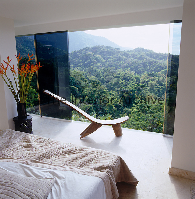 The sliding glass wall gives an amazing view of the jungle from the bed in this simple bedroom