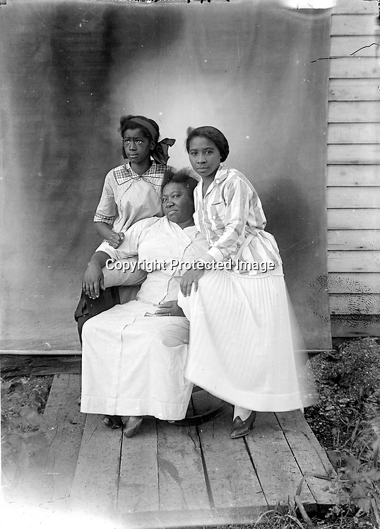 FLORENCE JONES, KIT CARRIGER, AND FRIEND. At left is Florence Jones; at right is probably Elenora &quot;Kit&quot; Carriger (later Evans). The older woman may be Kit's mother, Alice. Kit Carriger (1893-1981) married George Evans (1874-1945) around 1919. They were very active in Newman Methodist Episcopal Church. George was a charter member of Lincoln's black Masonic lodge and worked for many years as a chauffeur and houseman for C. B. Towle, a manufacturer. Widowed for 36 years, Kit cooked for a fraternity.<br /> <br /> Photographs taken on black and white glass negatives by African American photographer(s) John Johnson and Earl McWilliams from 1910 to 1925 in Lincoln, Nebraska. Douglas Keister has 280 5x7 glass negatives taken by these photographers. Larger scans available on request.