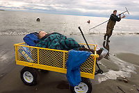 "Austin Earns, of Wasilla, Alaska, pulls a salmon dipnet from the Kenai River as his son Boone, 2, catches a nap in a utility trailer parked on the river bank at its mouth on Cook Inlet in Kenai, Alaska. ""We come down every year,"" Earns' wife Emily (not pictured) said. ""It's our annual trip. We like to usually get our limit. It's fun."""