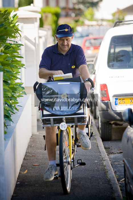 Postman Jacques Tapon rides his bicycle on his daily route in Montbazon, France, 25 June 2008. Tapon rides 17km a day in all seasons, 6 days a week for 21 days a months. With 5 weeks off every year, that amounts to a total of 3,774km a year.