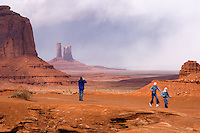 Swallowed by a massive landscape, Darren Schutz, left, of Melbourne, Australia, makes a photograph while daughters Lauren, 12,  and Alana, 8, run across a red sandstone outcrop at John Ford's Point at the Monument Valley Navajo Tribal Park in southern Utah, Friday, March 10, 2006. The stunning vistas in the park, stars in many John Ford westerns, are an often-forgotten destination for American travelers. (Kevin Moloney for the New York Times)