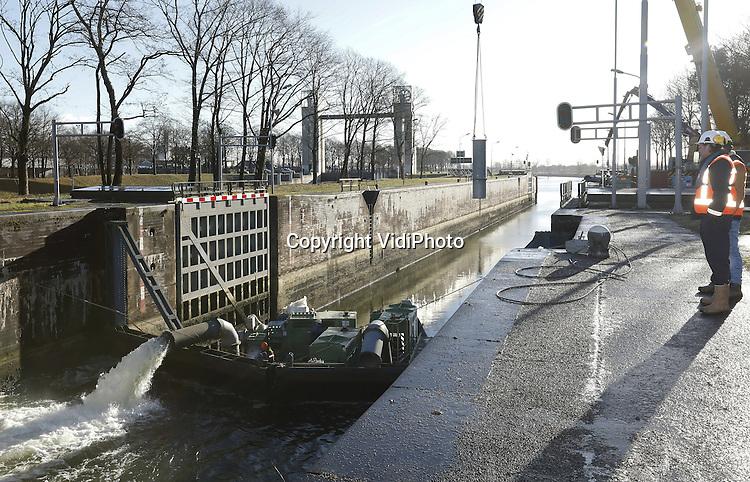 Foto: vidiPhoto<br /> <br /> HEUMEN - Onder toezicht van Rijkswaterstaat wordt donderdag flink doorgewerkt om een derde noodpomp te installeren, zodat scheepvaart op het Maas-Waalkanaal weer beperkt mogelijk is. Sinds de twee noodpompen maandag in werking zijn gesteld, stijgt het waterpeil in het Maas-Waalkanaal met circa 12 cm per etmaal. Het peil mag niet te snel stijgen. Er moet worden voorkomen dat een 'vloedgolf' het kanaal wordt ingepompt die schade veroorzaakt aan sluisdeuren en kanaalwanden. Daarom is Rijkswaterstaat aanvankelijk met twee noodpompen gestart. Dijken die deels drooggevallen waren zuigen nu weer water op. De hoeveelheid weggelopen water is moeilijk in te schatten; mogelijk is er meer water uit het kanaal weggelekt dan er oorspronkelijk was berekend. De peilstijging van het kanaal wordt nauwkeurig gemeten. De derde pomp wordt geplaatst op hetzelfde ponton waar de andere twee pompen op staan. Met deze derde pomp stijgt de capaciteit van 10 miljoen liter per uur naar 15 miljoen liter per uur. Tijdens de werkzaamheden moesten de andere pompen even uitgeschakeld worden. Met de ingebruikname van derde pomp kan er naar verwachting eind deze week weer beperkt scheepvaartverkeer plaatsvinden op het Maaswaal-Kanaal, dat na de aanvaring bij de stuw in Grave afgesloten moest worden. Voor de sluizen bij Weurt liggen 25 schepen met lading voor het buitenland te wachten. Het schutten nu zou teveel water uit het Maaswaal-Kanaal trekken, met grote gevolgen voor de daar liggende woonboten.