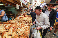 Israel,Jerusalem, an orhodox jude man is choosing the challah bread for the Shabbat in   the Mahane Yehuda Open Air Food Market,