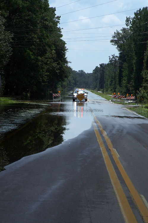 A county sheriff mans a flooded intersection.