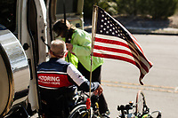 Morehead City, NC -- An American flag flies from the cycle of quadriplegic hand cyclist Paul Kelly, 62, who trains for the Boston Marathon Tuesday, March 27, 2018. (Justin Cook for The Wall Street Journal)<br /> <br /> SUMMARY:<br /> <br /> Paul Kelly, hand cyclist, Beaufort, NC Training for the Boston Marathon so we would want to shoot in March to run the week before the marathon or marathon Monday, Apriln16. Life as a quadriplegic doesn't keep 62-year-old Paul Kelly on the sidelines. After breaking his neck in a swimming accident in 1978, Kelly was determined to find fitness activities to maintain an active lifestyle. He discovered handcycles while watching his niece compete in the 2006 Marine Corps Marathon and was inspired to start his own marathon career to stay fit. Paul has competed in over 100 half and full marathons. On April 16, he will celebrate his 40th year of living as a quadriplegic by taking on one of the most coveted races for a marathoner -- the Boston Marathon. Kelly is among the 60 handcyclists competing in the 2018 Boston Marathon with a qualifying time of 1:26:37. Most of Paul's distance training takes place at Bogue Banks, which includes Atlantic Beach, Salter Path, and Emerald Isle, N.C. It's Nicholas Sparks worthy scenery with its marshes, waterways, inlets and small islands. Paul is particularly fond of the approach from Atlantic Beach to Bogue Banks -- it's via the high-rise bridge. In cold weather, Paul has to be mindful of the environment and dress in a manner that insulates his legs while also allowing his upper body to ventilate. Paul chooses to train at times of day when the temperatures are more reasonable. He uses hand warmers in his gloves, on the inside the grips on his handcycle and in the legs of his trousers.