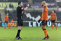 (L-R) Referee Achristopher Kavanagh shows a yellow card to Romain Saiss of Wolverhampton Wanderers during the Emirates FA Cup match between Swansea and Wolverhampton Wanderers at the Liberty Stadium, Swansea, Wales, UK. Wednesday 17 January 2018