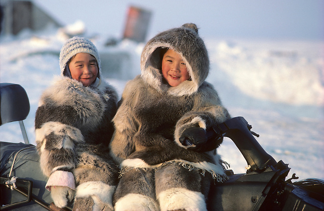 Inuit children dressed in furs play on a snowmobile..Igloolik, Nunavut, Canada.
