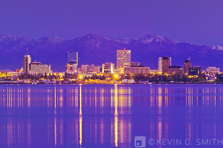 View of downtown Anchorage skyline across Knik arm, city lights reflected in the water, shot from the port at Point Mckensie. Kenai mountains in background. Fall, twilight, Anchorage Alaska.