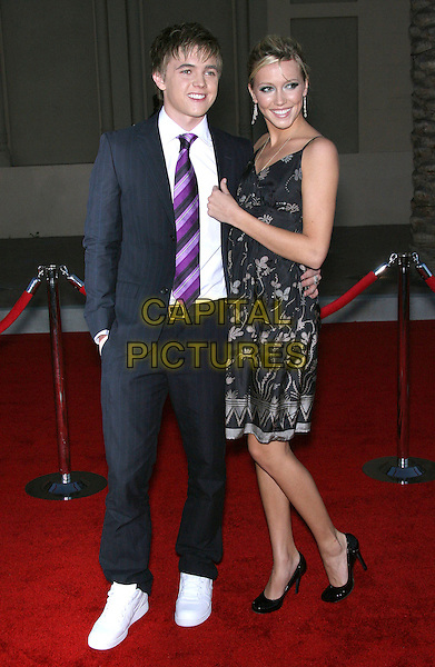 JESSE McCARTNEY & KATIE CASSIDY.34th Annual American Music Awards - Arrivals held at the Shrine Auditorium, Los Angeles, California, USA..November 21st, 2006.full length black suit dress floral print.CAP/ADM/ZL.©Zach Lipp/AdMedia/Capital Pictures
