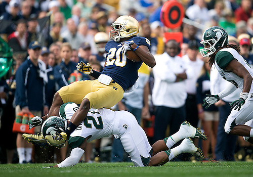 September 21, 2013:  Notre Dame wide receiver C.J. Prosise (20) is tackled by Michigan State cornerback Justin Williams (21) during NCAA Football game action between the Notre Dame Fighting Irish and the Michigan State Spartans at Notre Dame Stadium in South Bend, Indiana.  Notre Dame defeated Michigan State 17-13.