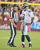 Seattle Seahawks quarterback Russell Wilson (3) shows one of the officials how far behind the line of scrimmage he was during a challenge by the Washington Redskins in the fourth quarter of the game at FedEx Field in Landover, Maryland on Monday, October 6, 2014.  The Seahawks won the game 27 - 17.<br /> Credit: Ron Sachs / CNP