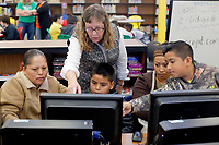 NWA Democrat-Gazette/DAVID GOTTSCHALK Theresa Thompson, librarian media specialist at Eastside Elementary School, leans in to help Esteban Morales (from right), a fourth grade student, and his mother Maria, Gabriel Sanchez, a fourth grade student, and his mother Lizeth Rojas, during Coding and Creating Together Friday, November 30, 2018, inside the library at the school in Rogers. The school participated in a week long coding exercise in anticipation of participating in the International Hour of Code taking place next week.
