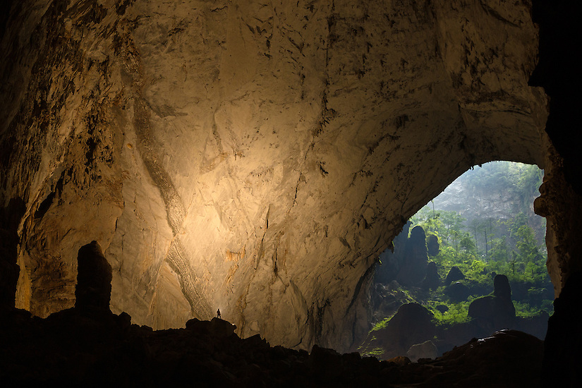 A caver stands in a passage way in Hang Son Doong with the second doline off in the distance.