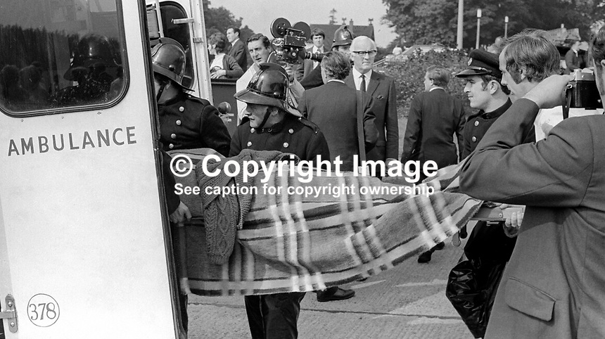 Injured office worker is stretchered to an ambulance following the explosion of a Provisional IRA bomb at the Belfast headquarters of the N Ireland Electricity Board. One man died in the blast and 35 others were injured. 25th August 1971. 197108250377a.<br />