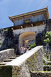 Visitors walk through the Kyukeimon gate which is located  inside the Shuri-jo Castle Park in Naha, Okinawa Prefecture, Japan, on June 25, 2012. The arch-stoned gate topped with wooden roof tiles was predominantly used by women. Photographer: Robert Gilhooly