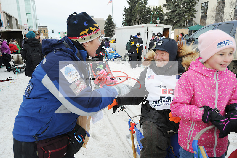 Iditarod Trail Sled Dog Race veteran Jim Lanier of Chugiak chats with race veterinarian Kim Henneman at the  ceremonial start of the 1,000-mile race in Anchorage, Alaska Saturday, March 5, 2016. At right is Lanier's granddaugher Jessie Horning. Photo for the Star by Michael Dinneen